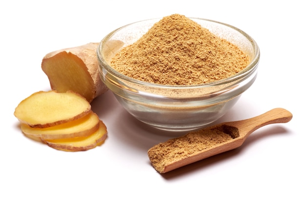 Grinded organic ginger spice in ghass bowl isolated on white surface