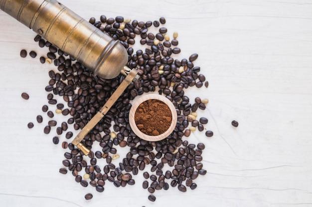 Измельчитель и молотый кофе на кофейных зернах