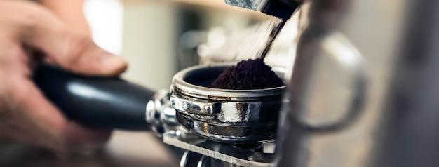 Grinder machine grinding coffee into portafilter