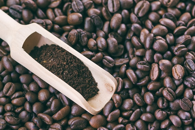 Grinding coffee beans in wood spoon on roasted coffee beans background to present coffee
