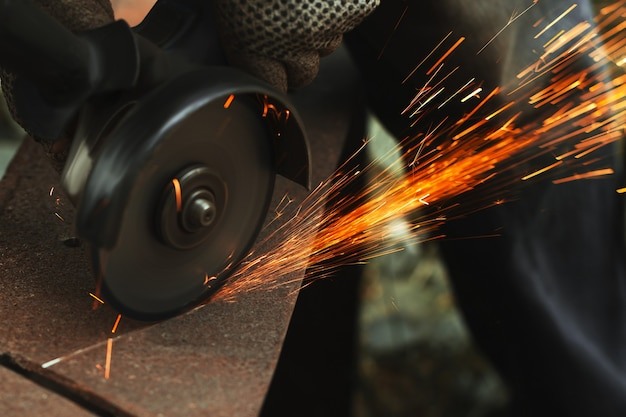 Grinding cutting metal sheet with angle grinder machine and sparks, close up.