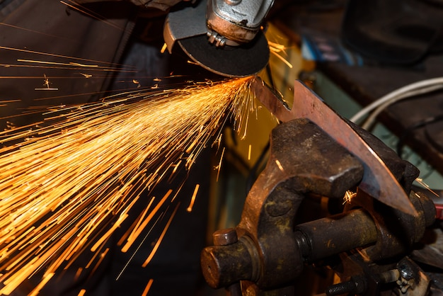 Grinding metal tools with sparkles - forge workshop