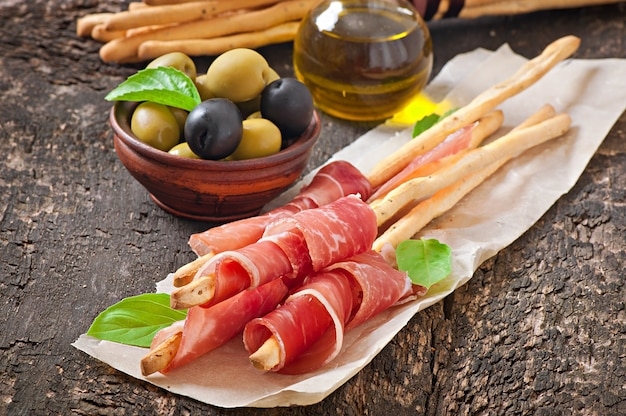 Grissini bread sticks with ham, olives, basil on old wood