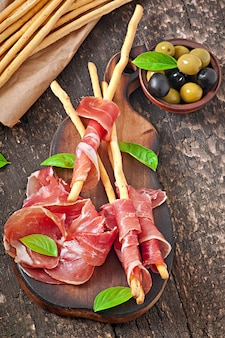 Grissini bread sticks with ham, olives, basil on old wooden surface