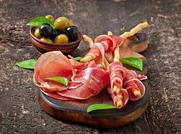 Grissini con prosciutto, olive, basilico su legno vecchio