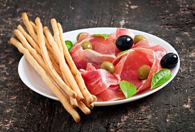 Grissini bread sticks with ham, olives, basil on old wooden