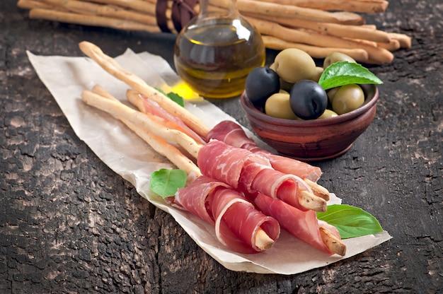 Гриссини с ветчиной, маслинами, базиликом на старом дереве
