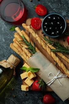 Grissini sticks, snacks and wine on black smokey background
