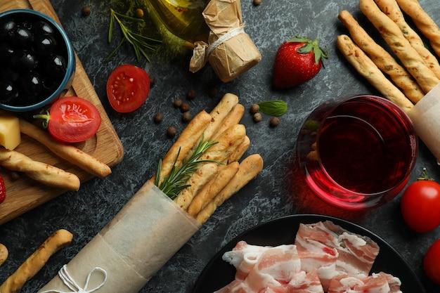 Grissini sticks, snacks and wine on black smokey surface