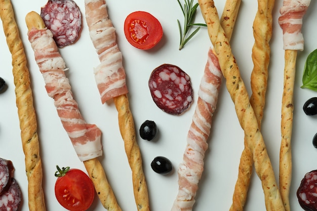 Grissini sticks with bacon and snacks on white surface