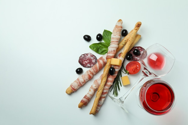 Grissini sticks with bacon, snacks and wine on white surface