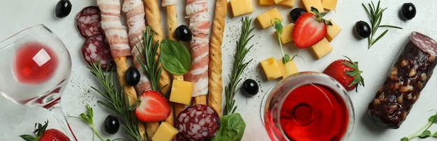 Grissini sticks with bacon, snacks and wine on white textured surface
