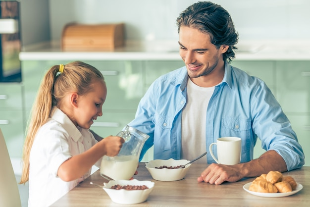 Grl and her father are having breakfast in kitchen at home.