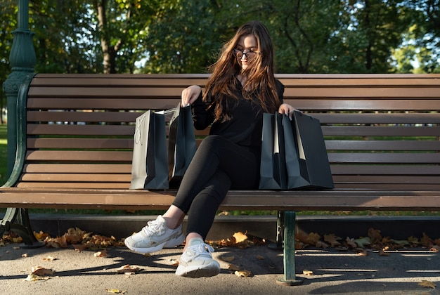 Grl с бумажными пакетами для покупок отдыхает на скамейке в парке и наслаждается покупками. удачных покупок.