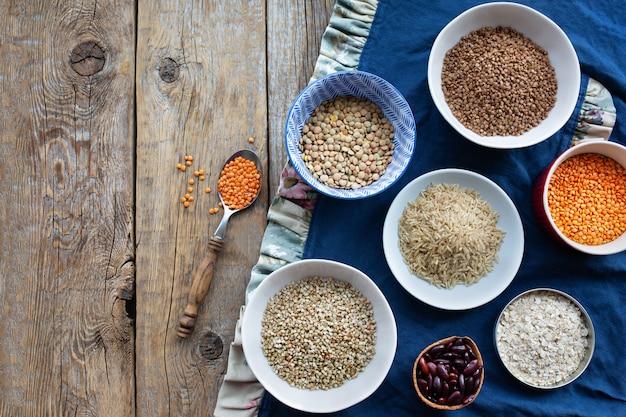 木製のテーブルのボウルの割り。乾燥した穀物とリネンのテーブルクロス。生そば、レンズ豆、米、豆、オートミール、エンドウ豆。上からの眺め。健康食品。適切な栄養。食品のコンセプト。ビーガン食品。