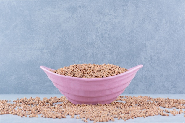 Groats spilled all over, with a full, pink bowl of buckwheat sitting in the middle on marble surface
