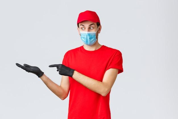 食料品とパッケージの配達、covid-19、検疫、ショッピングのコンセプト。フェイスマスクと手袋の興奮した興味をそそる宅配便は、小包の配達に割引またはプロモーションを導入し、バナーを手に持ってください