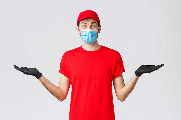 食料品とパッケージの配達、covid-19、検疫とショッピングのコンセプト。赤い制服を着た驚いた宅配便、手袋、フェイスマスク、横向きに手を繋いでいるバナーまたはキャリア会社のプロモーション