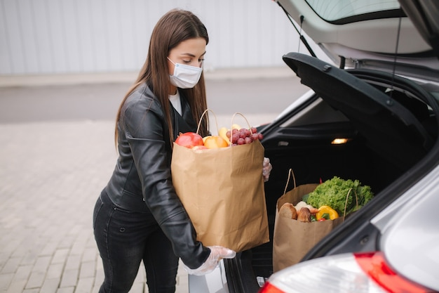 Groceries in female's hand by the car truck