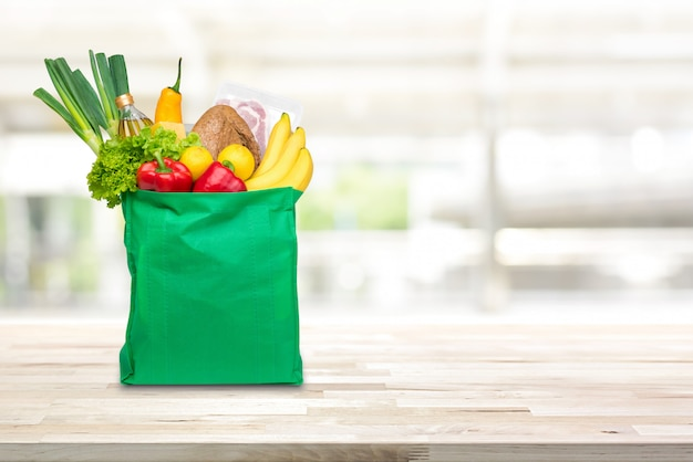 Groceries in green reusable shopping bag on wood table