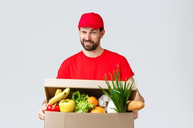 Consegna di generi alimentari e pacchi, covid-19, quarantena e concetto di shopping. bel corriere sorridente in uniforme rossa, fa l'occhiolino sfacciato mentre consegna una scatola di cibo, ordine online alla casa del cliente.