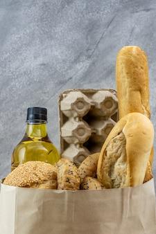 使い捨て紙袋に卵料理油と様々なパンが入った食料品の袋。パン屋さんの食べ物や飲み物、食料品の配達のコンセプトです。