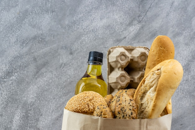 Grocery bag with egg cooking oil and variety of bread.