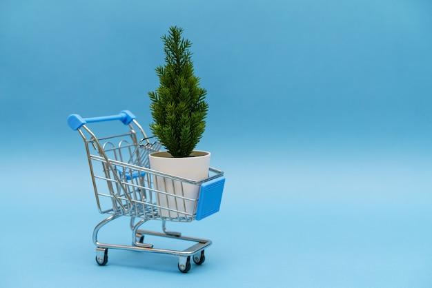 青い背景の食料品バスケット人工的なクリスマスツリークリスマスオンラインショッピング冬の休日...