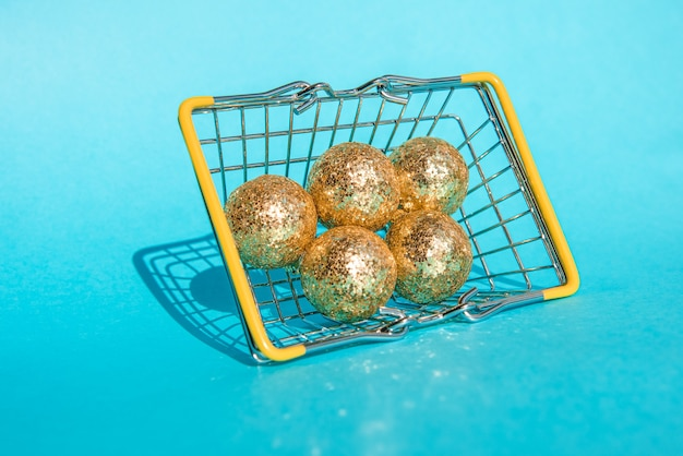 Grocery basket with christmas golden balls on a blue background place for your text