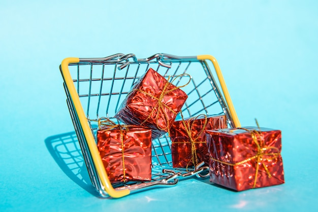 Grocery basket with gift boxes on a blue background place for your text
