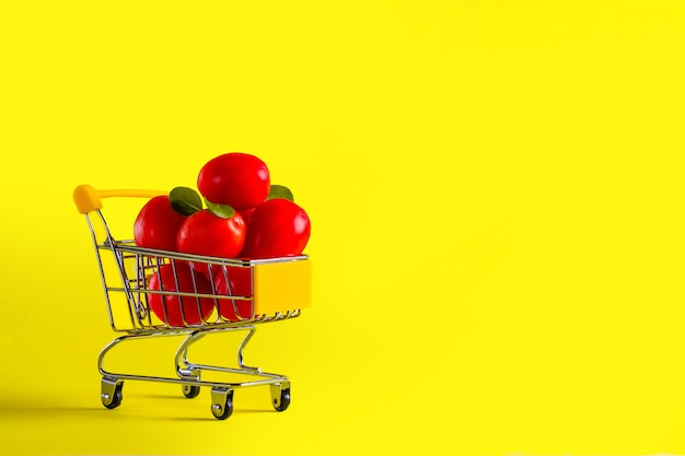 Grocery cart with cherry tomatoes and corn salad on a yellow background smart shopping