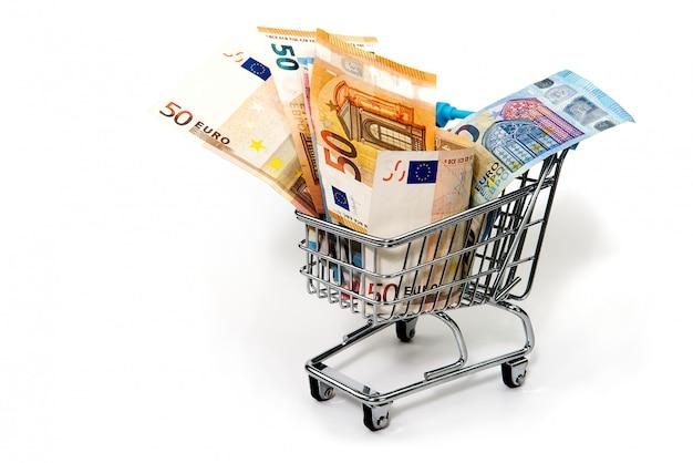 Тележка бакалеи при счеты евро изолированные на белизне. покупка, кредит, экономия денег, пенсия, концепция инвестиций