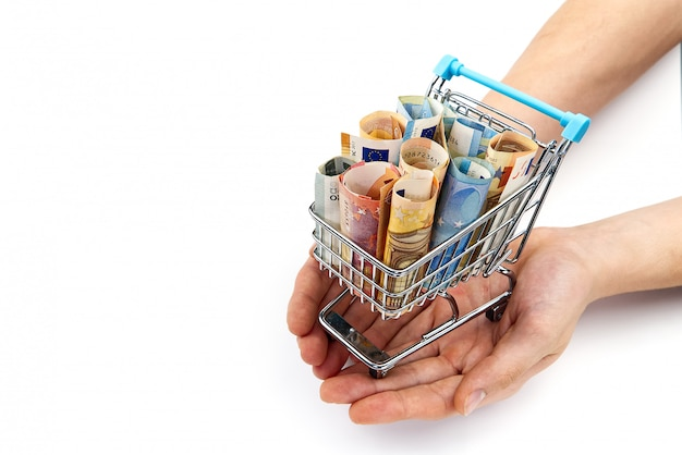 Grocery cart with euro bills with hand. isolated on white. shopping, loan, money saving, pension, investments concept