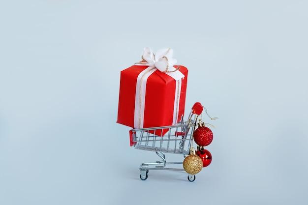 크리스마스 공 선물로 식료품 카트입니다. 온라인 상점에서 쇼핑. spase를 복사하십시오. 크리스마스.
