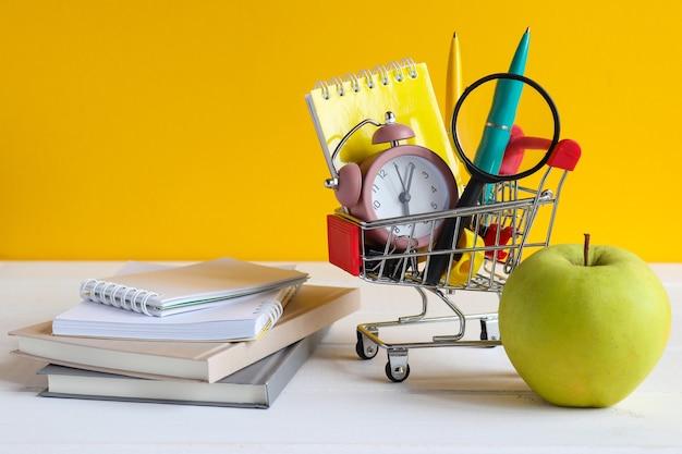 学用品が入った食料品カート青リンゴのメモ帳とテーブルの本学校の買い物 Premium写真