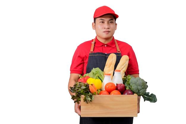 食料品、新鮮な果物や野菜が入った食料品箱が付いた赤い制服を着た食料品配達宅配便の男。