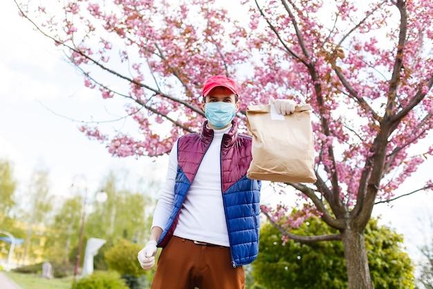 医療用手袋とフェイスマスクを着用した食料品配達人。食料品、ワイン、食品のオンラインショッピングと配送。コロナウイルスパンデミック時の自己検疫。フードデリバリーサービス宅配便
