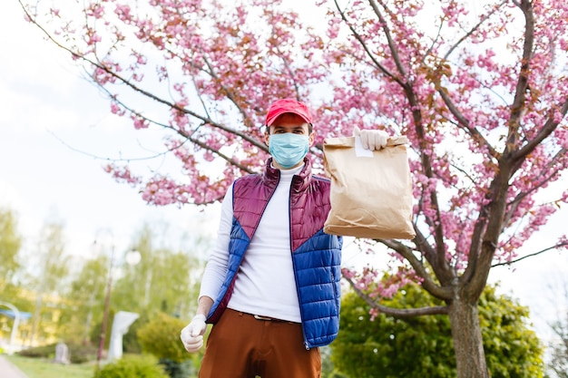 Grocery delivery man wearing medical gloves and face mask. online shopping and delivery for grocerys, wine and food. self quarantine during coronavirus pandemic. food delivery service courier