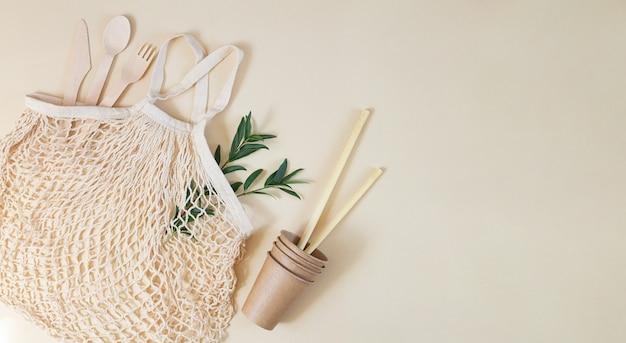 生分解性のカトラリー、紙コップ、竹のストロー、緑の葉が入った食料品エコメッシュバッグ。