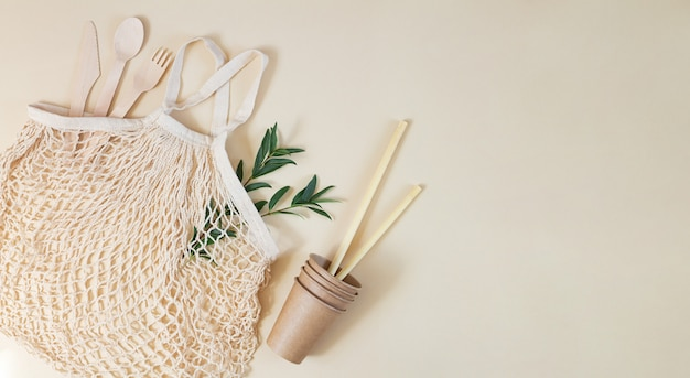 Grocery eco mesh bag with biodegradable cutlery, paper cups, bamboo straws and green leaves.