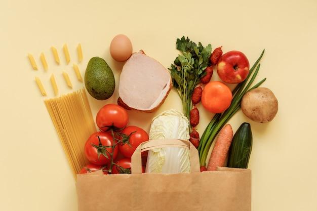 Бакалея, продукты питания на бумажной сумке на светло-желтом фоне.