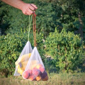 Продуктовая сетка с фруктами в руке на фоне природы