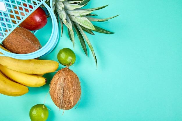 青色の背景に有機のエキゾチックなフルーツと食料品の買い物袋