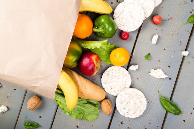 Grocery shopping . different food in paper bag on wooden .  flat lay.