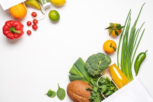 白い背景の上の食料品の買い物。紙袋に入った野菜、果物、ジュースボトル、パン