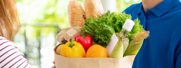 파란색 유니폼 식료품 가게 배달 남자 집에서 여자 고객에게 음식을 제공, 배너 크기