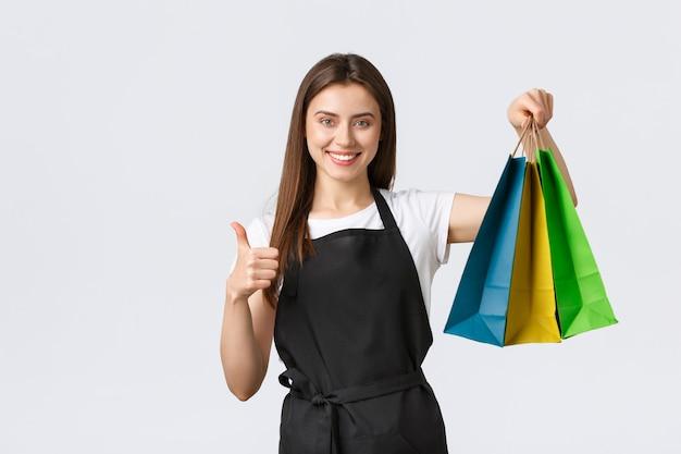 Работники продуктового магазина, бизнес и концепция кафе. симпатичная уверенно улыбающаяся продавщица в черном фартуке показывает палец вверх, гарантирует качество купленных товаров, держа бумажные пакеты с товарами.