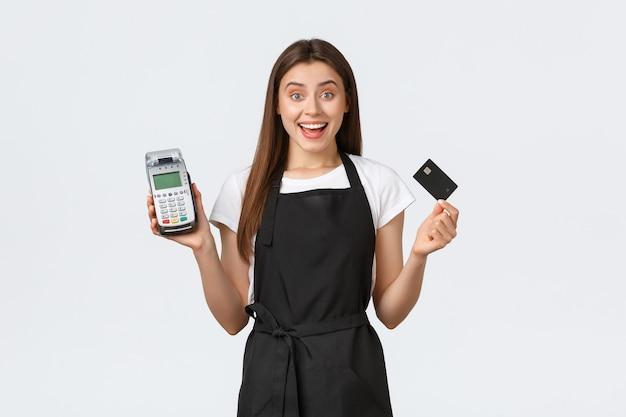 Работники продуктового магазина, бизнес и концепция кафе. взволнованный улыбающийся работник кафе, кассир в черном фартуке, демонстрирующий, как легко и безопасно покупать товары бесконтактно с помощью кредитной карты и pos-терминала