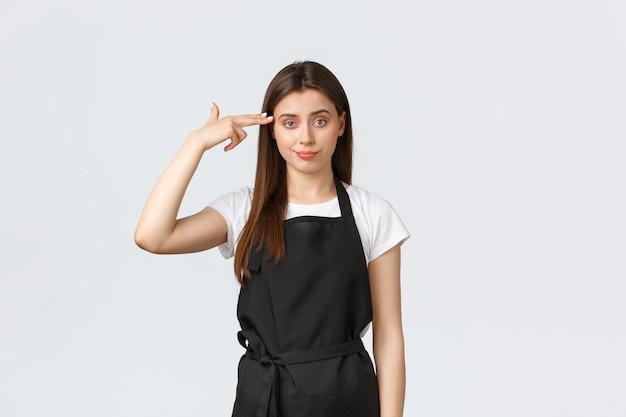 食料品店の従業員、中小企業、コーヒーショップのコンセプト。黒のエプロンでイライラして疲れた女性のバリスタが頭に偽の銃を向けてイライラし、懐疑的で気になります