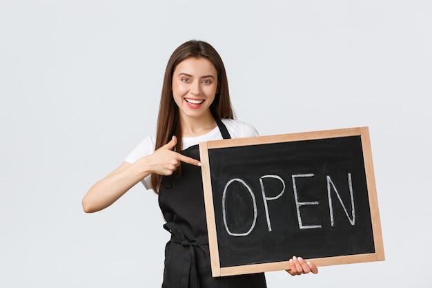 Работники продуктового магазина, малый бизнес и концепция кафе. веселая милая женщина-бариста в черном фартуке, указывая на открытый знак, приглашая прийти насладиться напитками в кафе, стоя на белом фоне